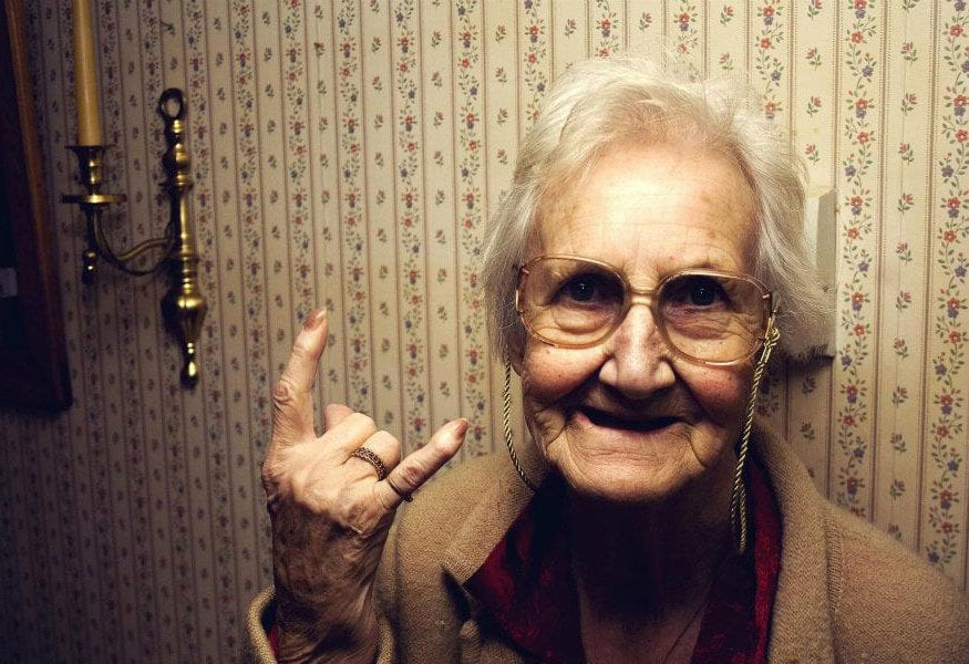 Happy retired grandma doing devil-horns hand gesture